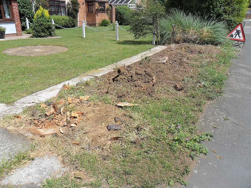 Cleared shrubbery and prepared area by adding weed protective membrane and new top soil.