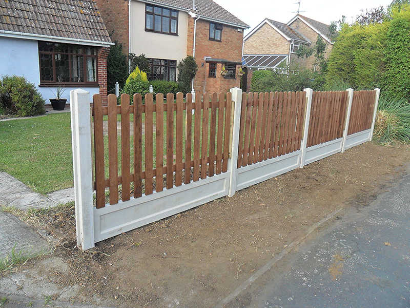 Installation of new picket fence using concrete posts and gravel boards.