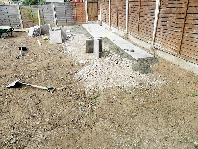 Installing paving slabs for new garden structures.