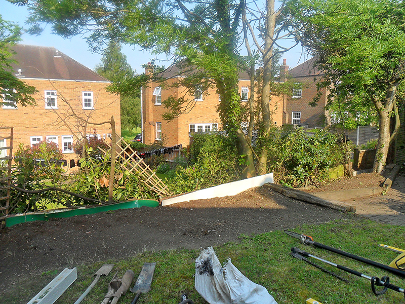 After removal of old fence, preparing for erection of new close boarded fence panels.