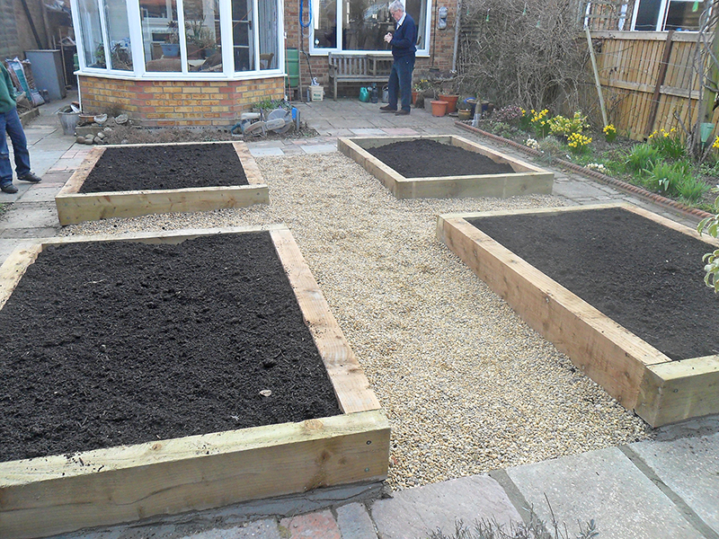 Filled beds with top soil and installed pathway with pea shingle gravel.