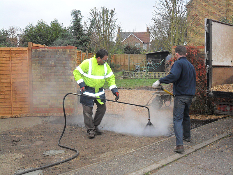 Spraying hot bitumen, readying for shingle application.